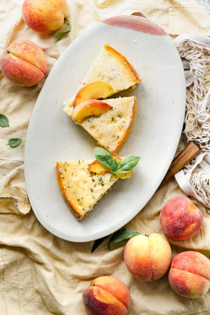 Three slices of peach cake on an oval plate next two yellow peaches.