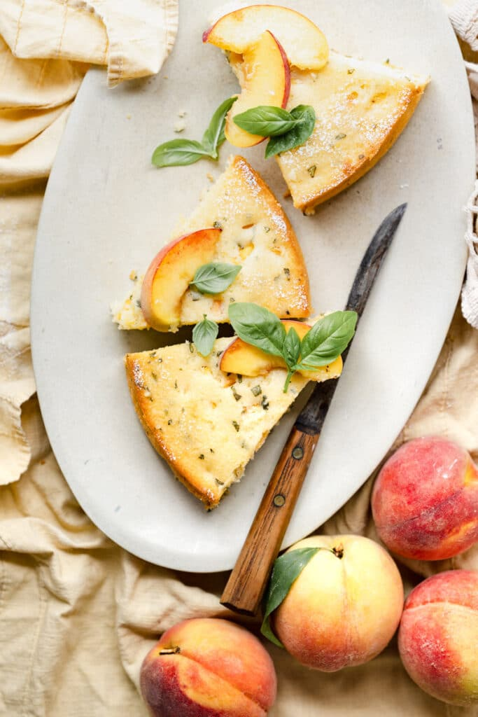 Three slices of peach cake on oval platter with knife.