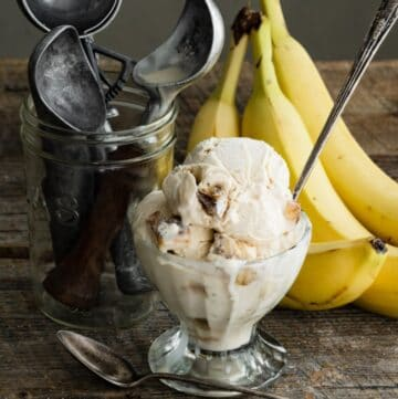 Closeup of a glass goblet filled with banana ice cream and a spoon next to bananas.