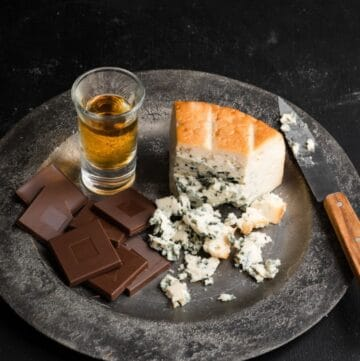 Milk chocolate squares, blue cheese, and a shot of bourbon on a metal plate.