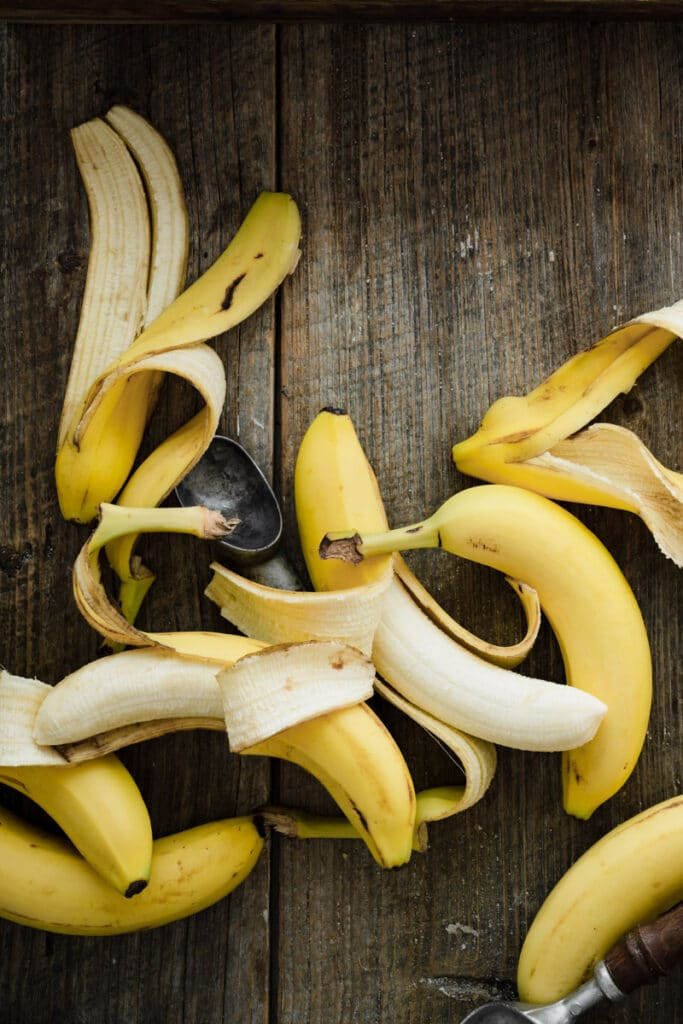 Several ripe bananas with peels on a wood table.