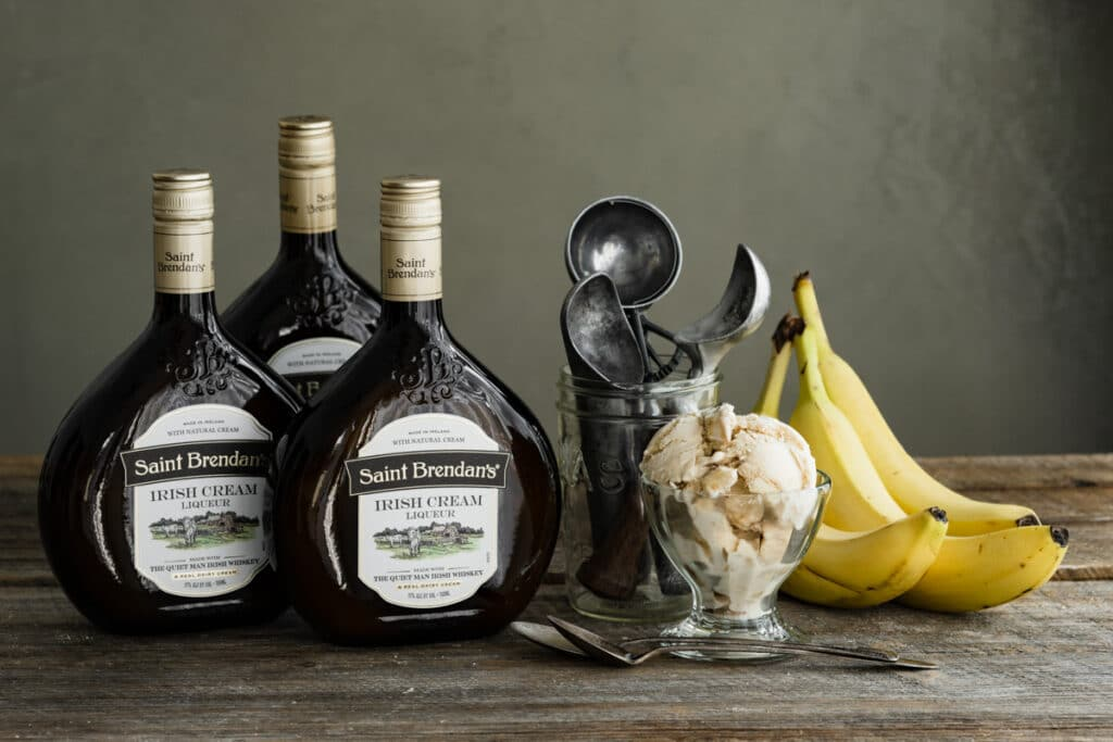 Three bottles or Irish cream on a table next to a bowl of ice cream and bananas.