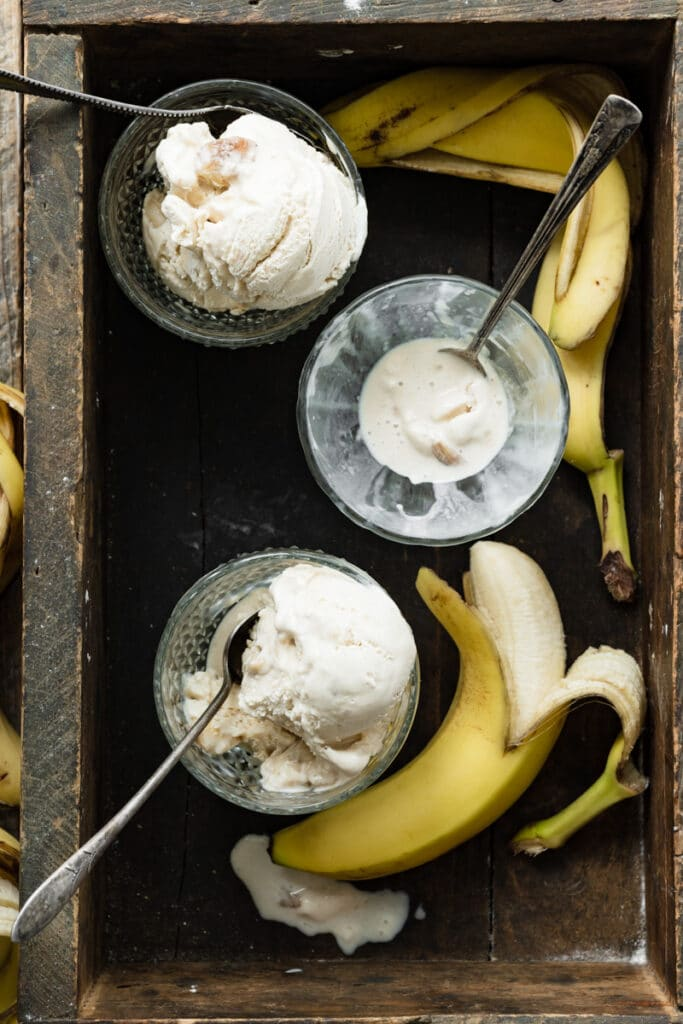Three bowls of ice cream in a wooden box with bananas.