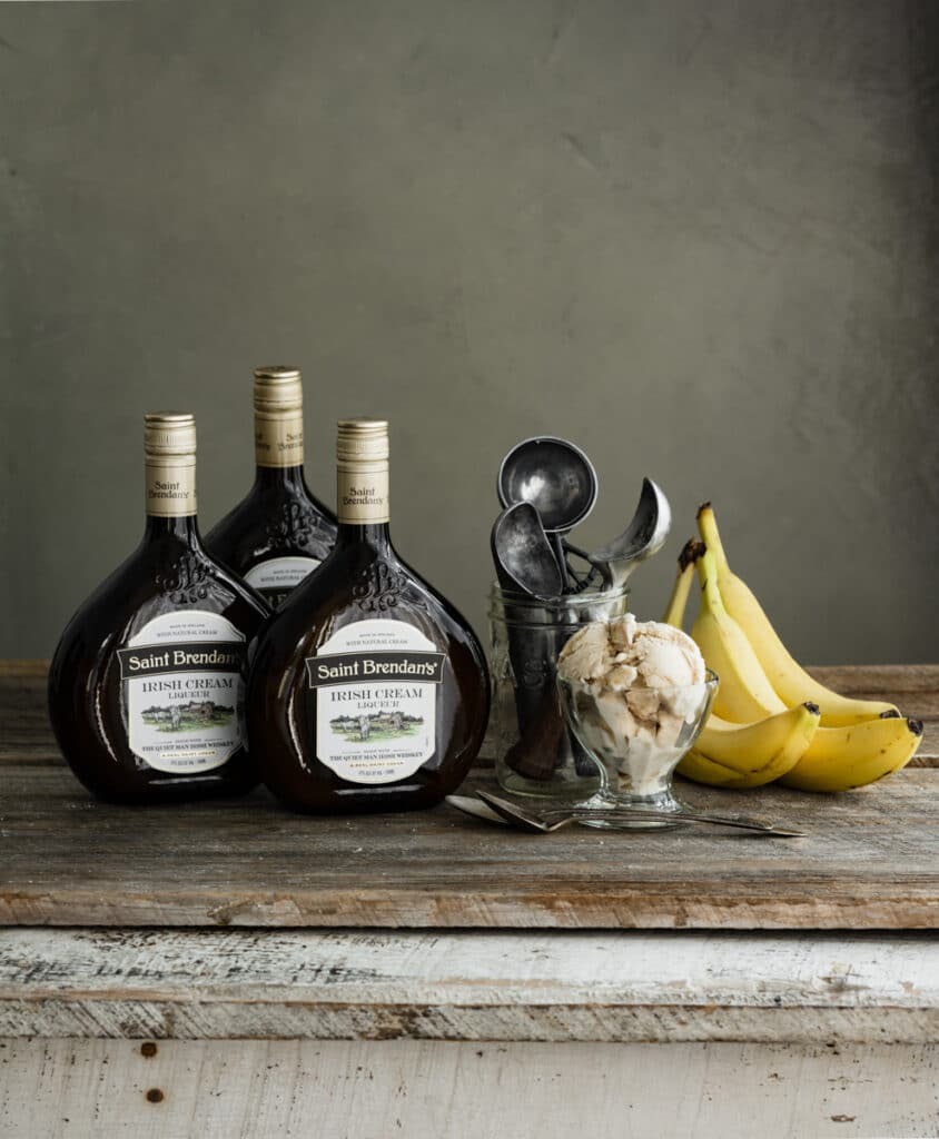 Bowl of ice cream on wood table next to  bottles of Irish cream and bananas.