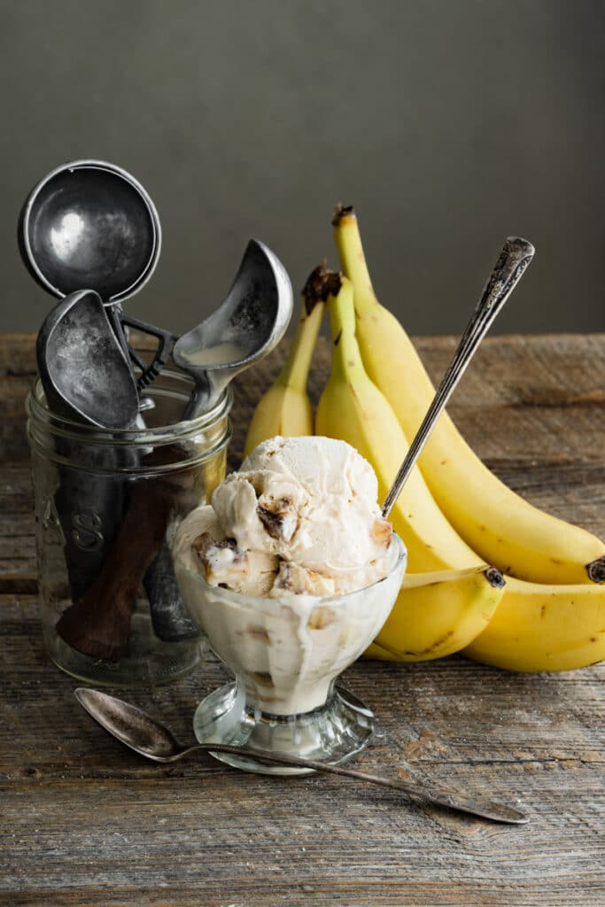 Glass bowl of ice cream next to jar of ice cream scoops and bananas on wood table.