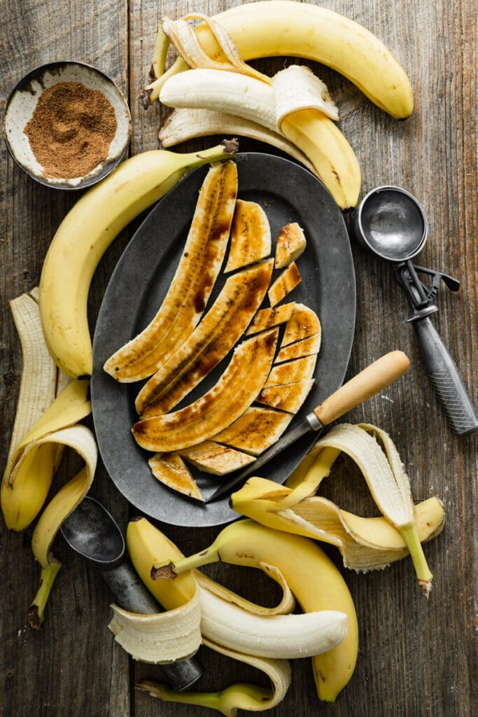 Brûlée bananas on an oval plate next to peeled bananas.