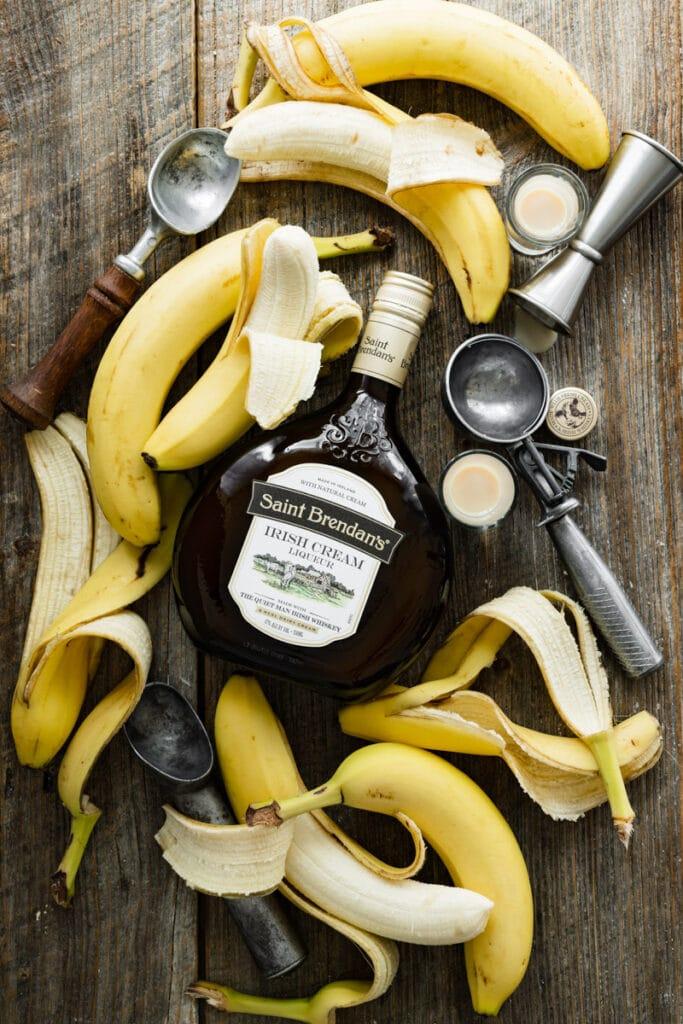 Bottle of Irish cream liqueur on a table next to peeled bananas.