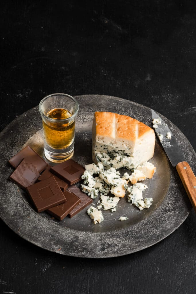 Chocolate, bleu cheese, and a shot of bourbon on a metal plate.