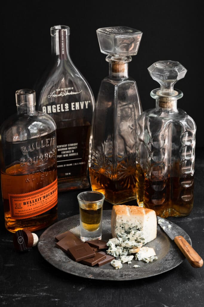 Bottles of bourbon next to a plate of chocolate and bleu cheese.