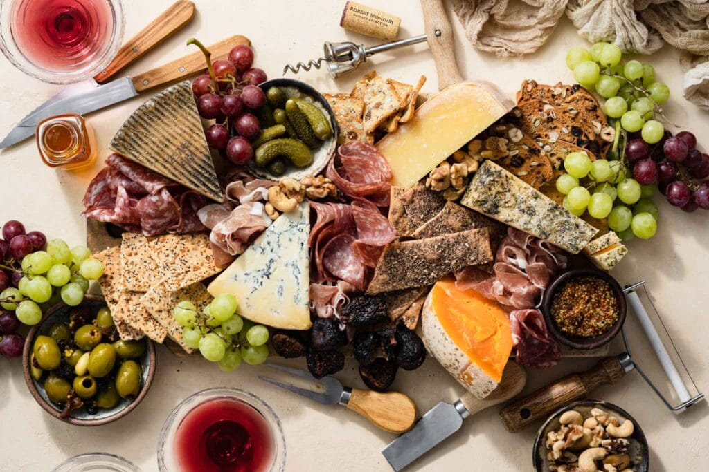 Charcuterie board with meats and cheese, next to glasses of red wine.