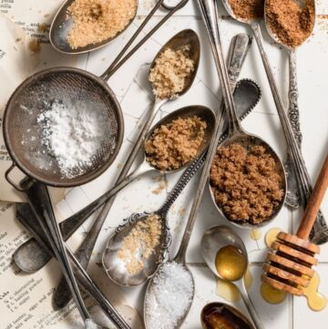 Spoons full of sugar and honey on a white tile counter.