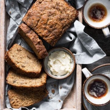 Sliced loaf of banana bread with butter and coffee on breakfast tray.