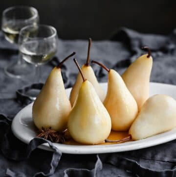 White poached pears on a oval plate next to glasses of wine.