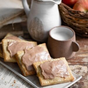 Tray of frosted pop tarts with glass and pitcher of milk on table.