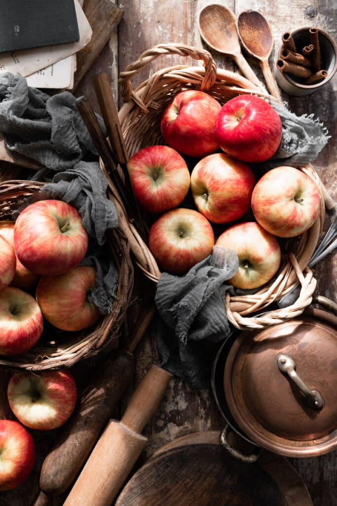Red apples in two baskets on a wood table.