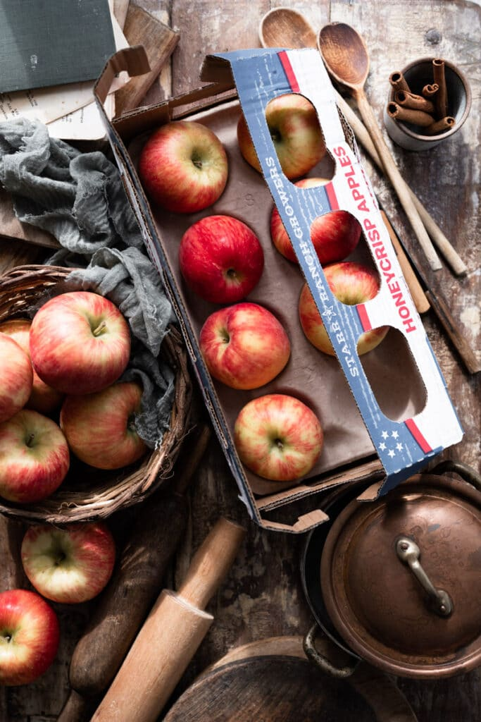 Box of red apples on table next to baking tools.