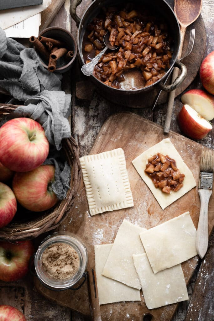 Pie dough cut into squares and topped with chopped apples on a cutting board.