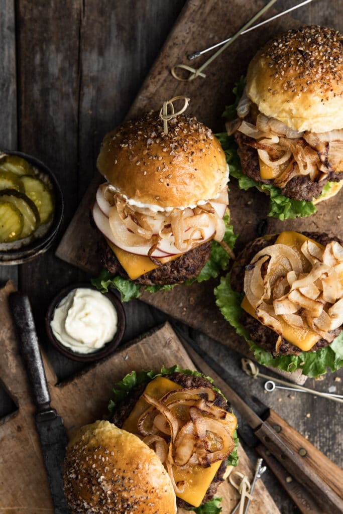 Four burgers on wood cutting boards with ingredients showing.
