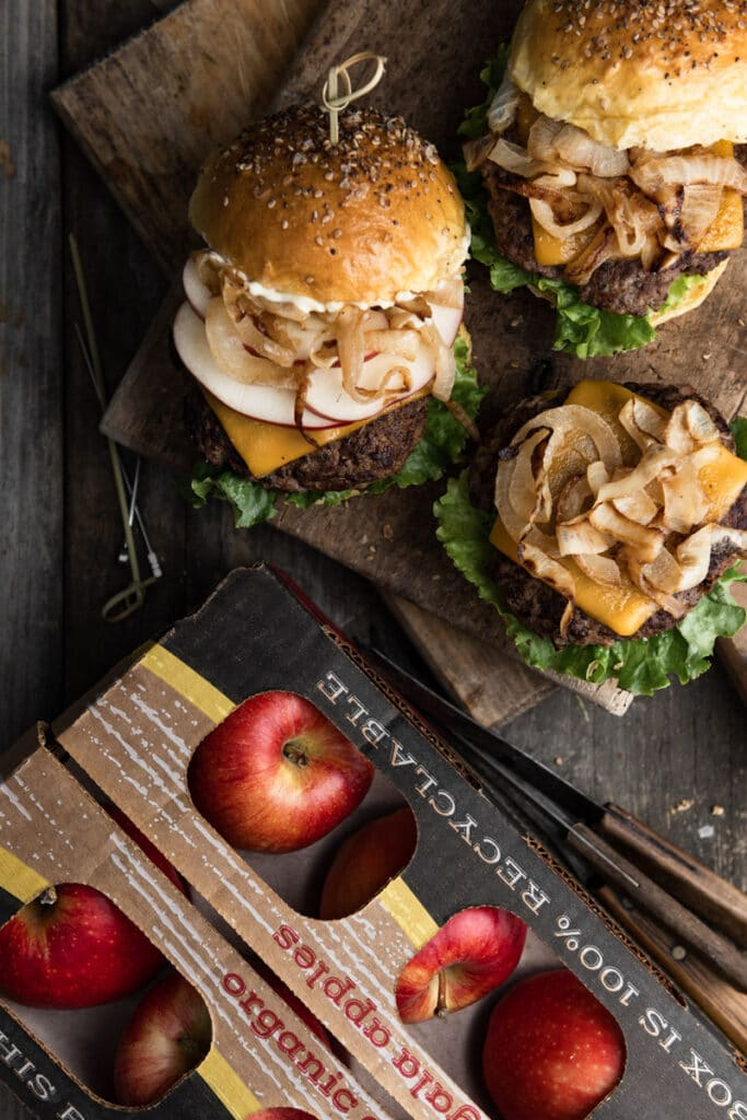 Burgers on a wood cutting board next to a box of gala apples.