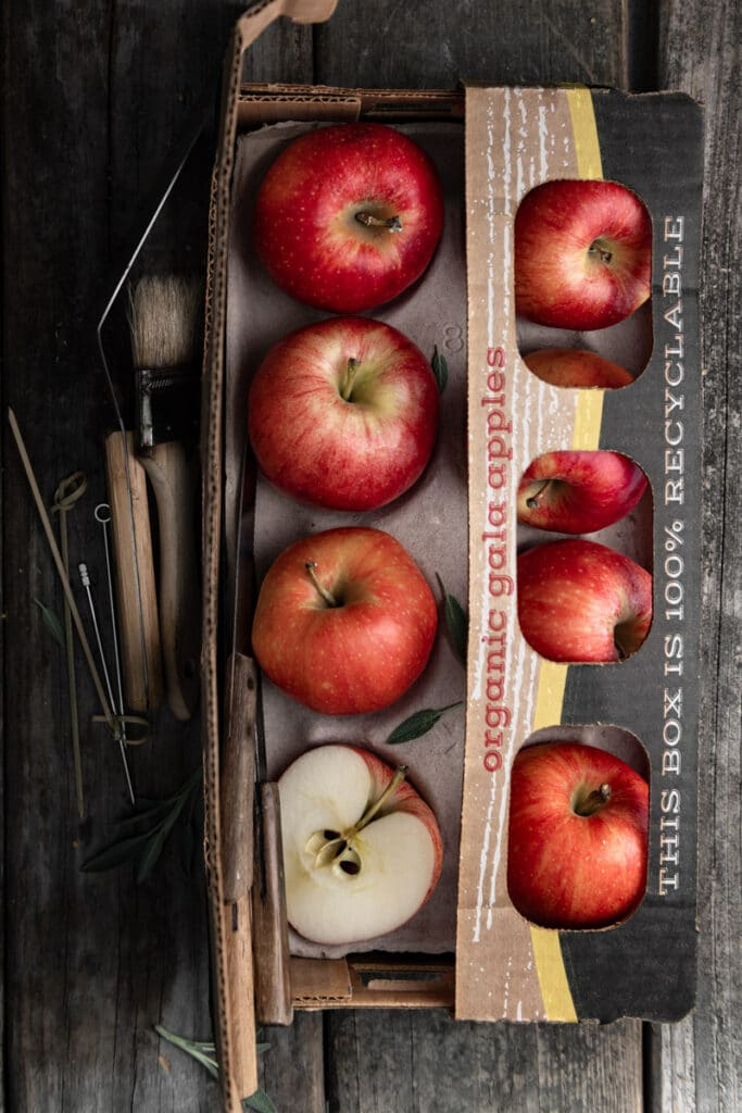 Gala apples in a cardboard apple box next to knives.