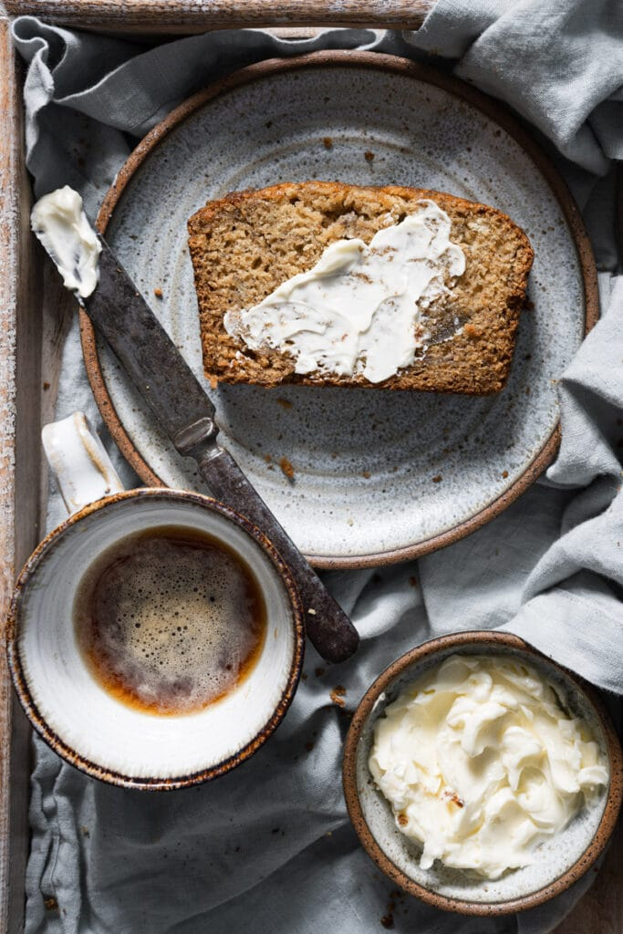 Slice of banana bread with butter on plate next to coffee.