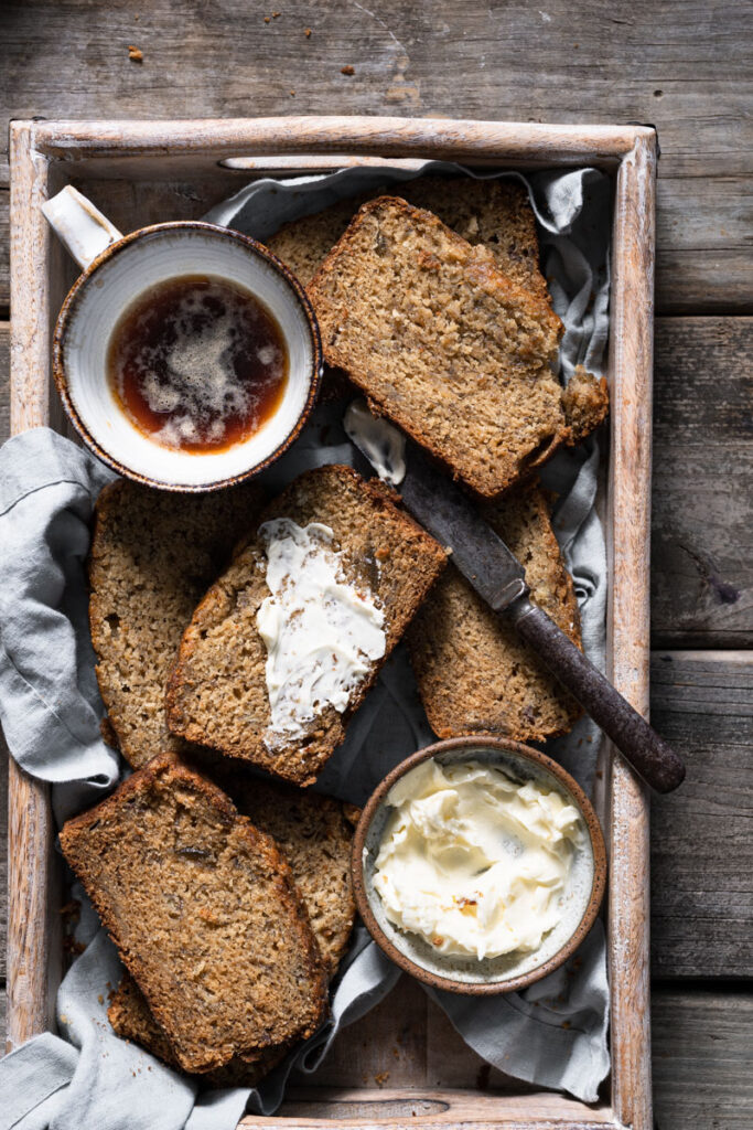 Slices of banana bread next to cup of coffee.