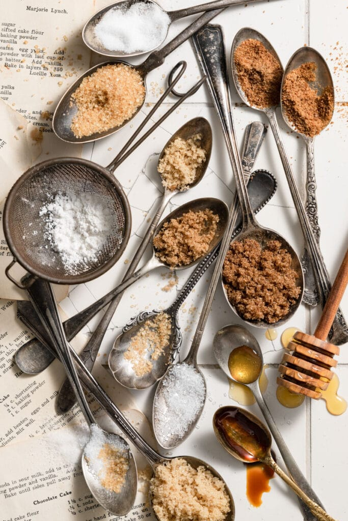 Lots of spoons filled with different types of sugar on a white tile counter.