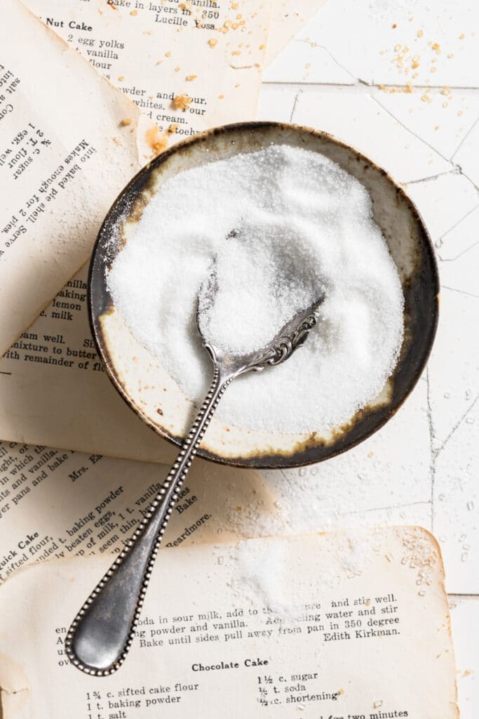 Bowl of granulated sugar with a spoon.